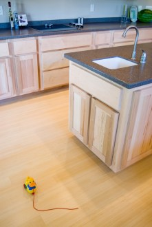 Its ok to mix woods. Try Natural bamboo next to Hickory, Birch, or Maple cabinets.
