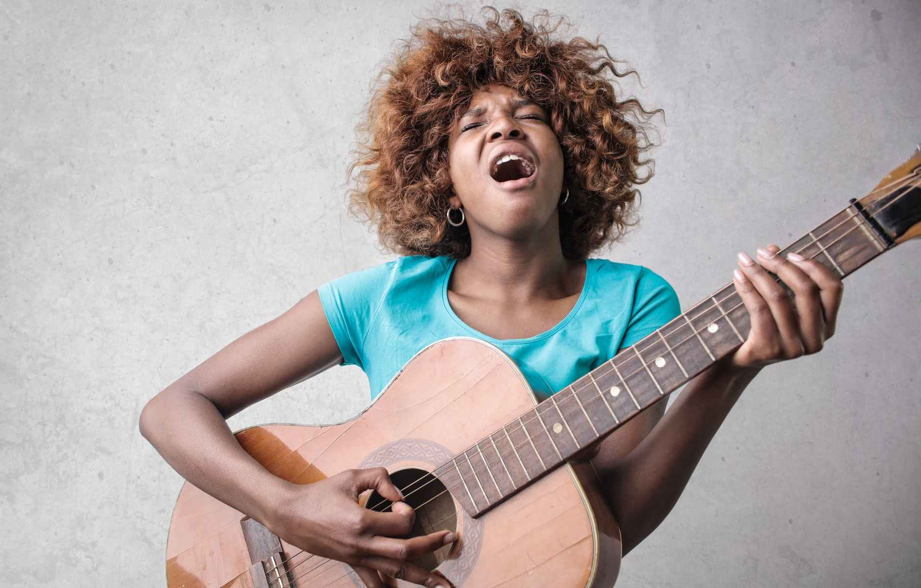 woman playing acoustic guitar while singing
