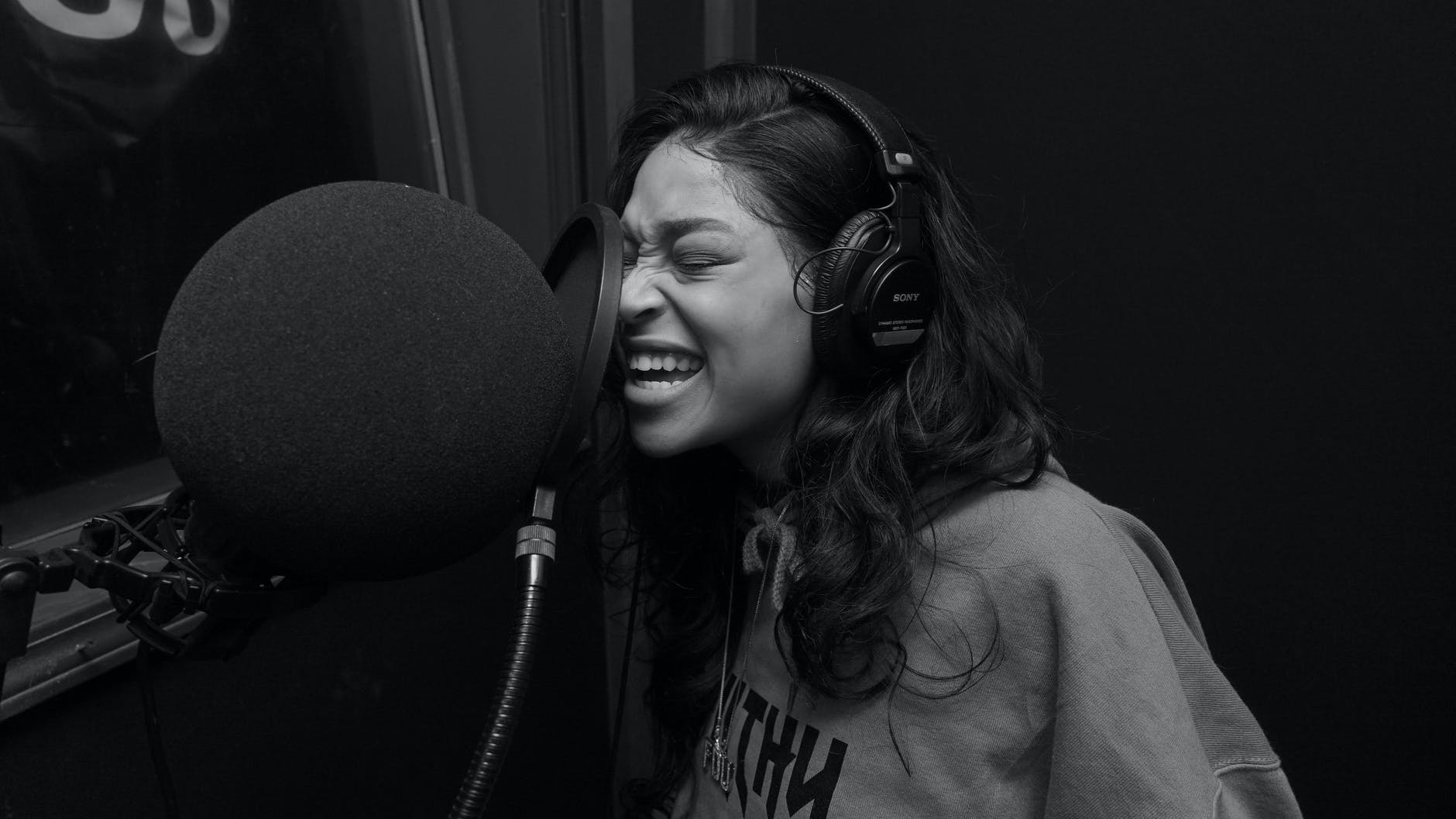 woman in gray crew neck shirt singing while wearing black headphones