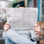 homem sentado lendo o boletim