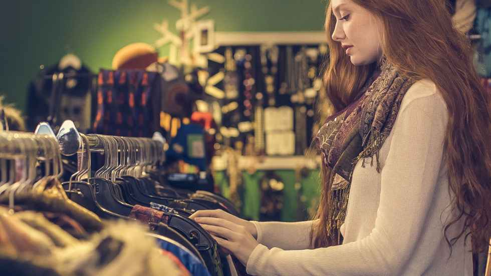 woman wearing white long sleeved shirt with scarf standing near clothes sold in second-hand store for slow fashion