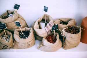 different types of beans in sacks with inscriptions for refill at zero waste shop to help your sustainable new year resolutions