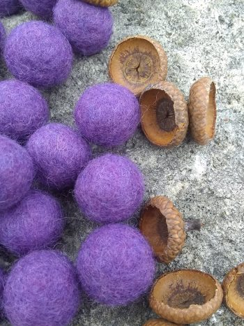 purple wool felt balls and rovings with acorn heads scattered beside