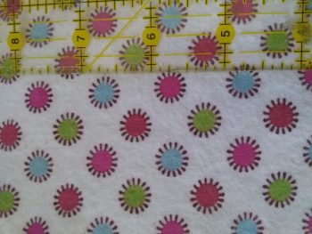 "white flannel with pattern of pink, red, blue and green dots, with measuring tape to show scale. Each dot 1/2"" diameter, spaced on 1"" centres."