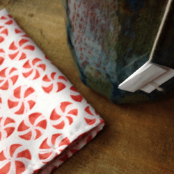 white cloth napkin with pattern of red peppermint candies, beside a pottery mug of tea
