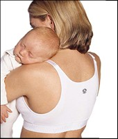 caucasian woman wearing nursing bra and cuddling sleeping infant.