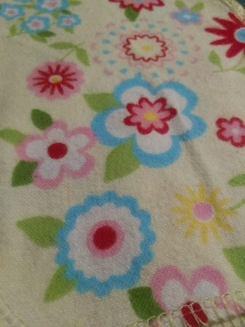 bright flannel with yellow background and pattern of flowers in pinks, blues and greens