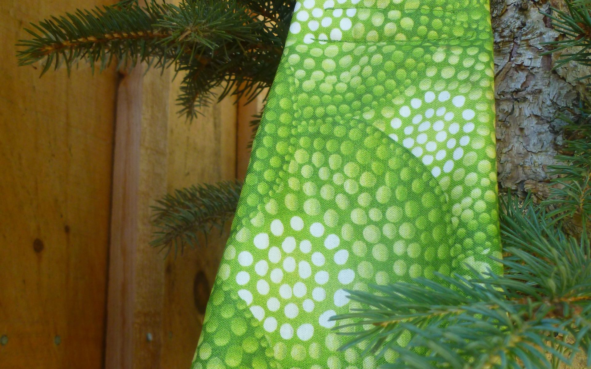 midwifery weigh sling made from spring-like shades of green in a circular dot pattern.