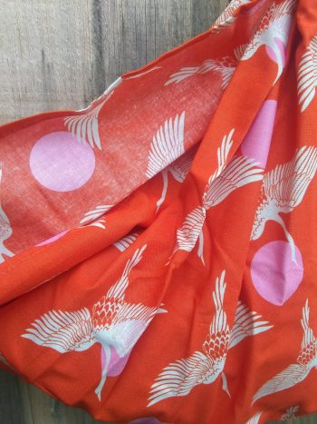bright orange weigh sling patterned in herons and pink suns, against barnboard wall