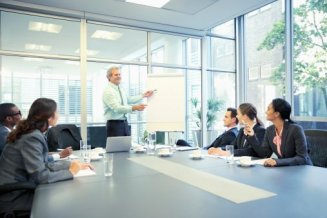 Businessman leading meeting at flipchart in conference room