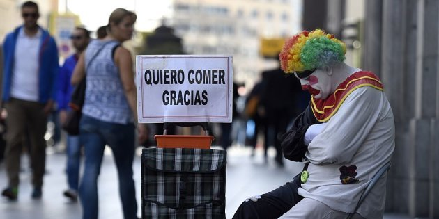 "Rayito, a beggar dressed as a clown sits next to a placard reading ""I want to eat, thank you"" in Gran Via street, in the centre of Madrid, on October 28, 2014.   AFP PHOTO/ GERARD JULIEN        (Photo credit should read GERARD JULIEN/AFP/Getty Images)"