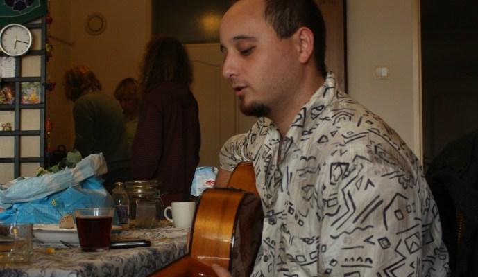 Jonge speelt gitaar na Karma Kitchen. Op de achtergrond staan drie jongeren af te wassen?