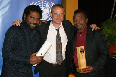 Three men holding an award