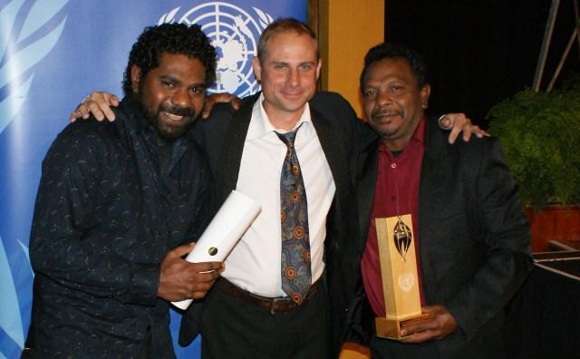 Three men holding an award