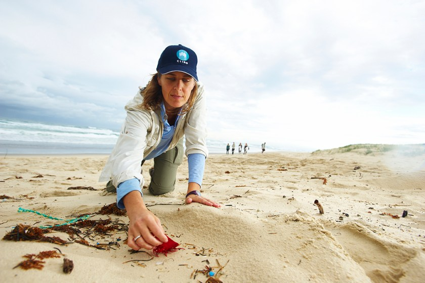 A woman on a beach picking up a piece of red plastic from sand