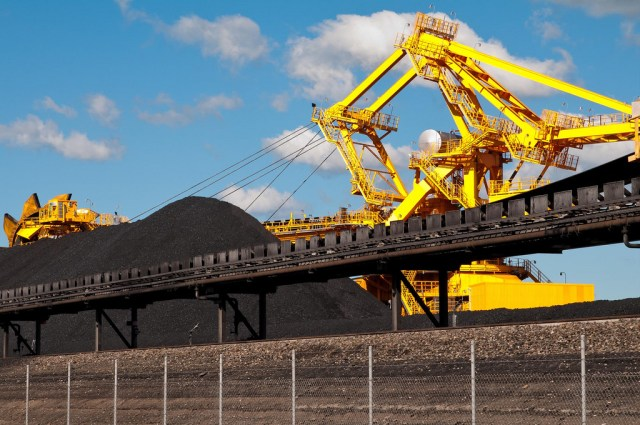 A large mound of coal with yellow machinery behind it