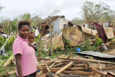 A woman holding a baby in front of a cyclone-damaged house in Vanuatu