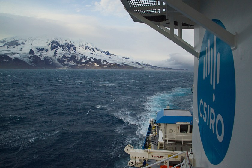 A ship sailing away from island with snow capped mountain