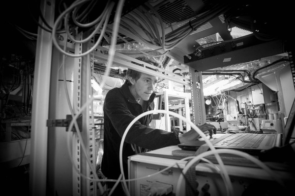black and white photo close up of man on laptop surrounded by shelves and equipment and wires