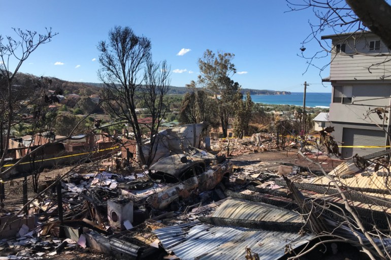 houses destroyed by fier with sea in the background