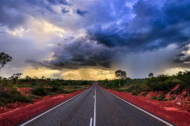 storm clouds over an outback highway fringed with red dirt