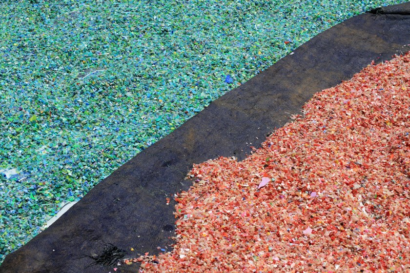 recycled plastics in small chips and separated, green on left and red on right