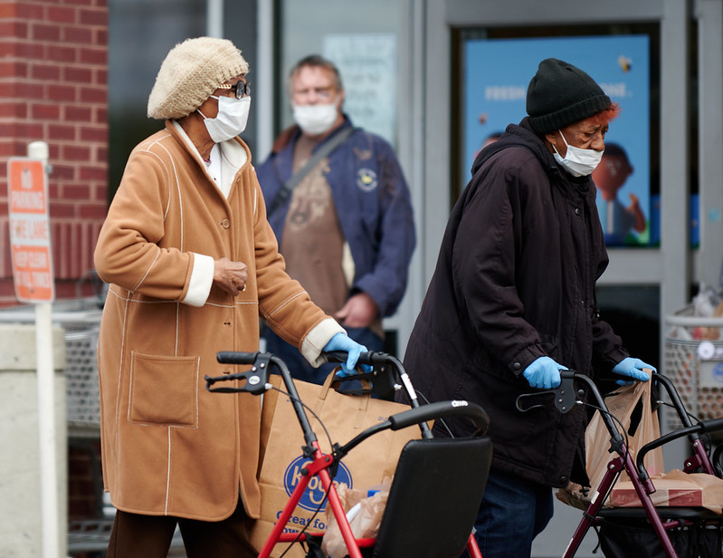 Picture of elderly women with walking frames and masks and gloves on. The women are grocery shopping in Richmond, Virginia. April 2020. Image by Ronnie Pitman/Flickr