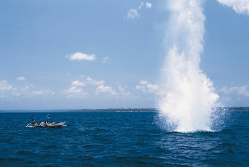A fishing boat (left) and a blast explosion in the water (right)