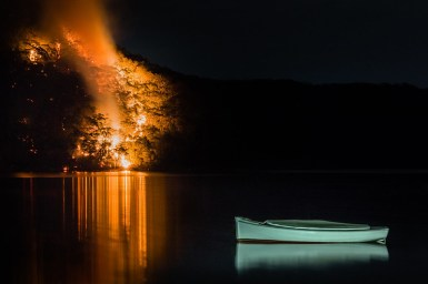 A boat sits on the water while the bush behind it (on the edge of the lake) is on fire.