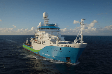 A blue, green and white painted research vessel on the open ocean.