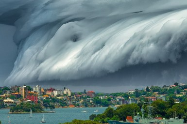 A large storm depicted by rolling grey clouds looms in the sky above Sydney Harbour. Image Richard Hirst.