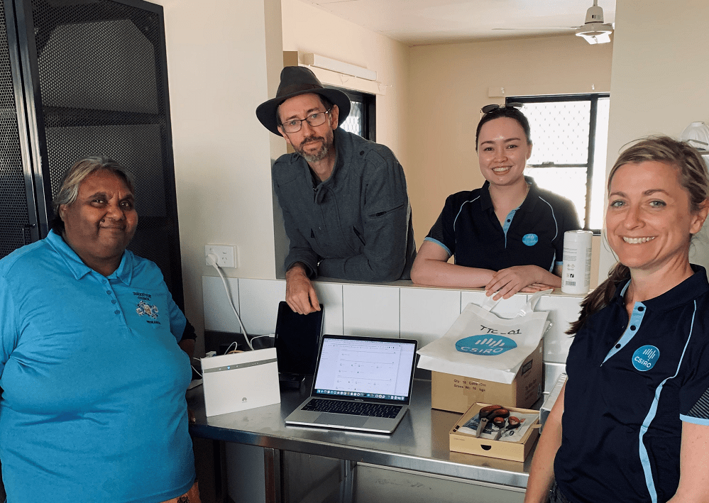 A group of four people, smiling at the camera surroundinig a laptop. Two of the people pictured are CSIRO researchers in polo shirts.