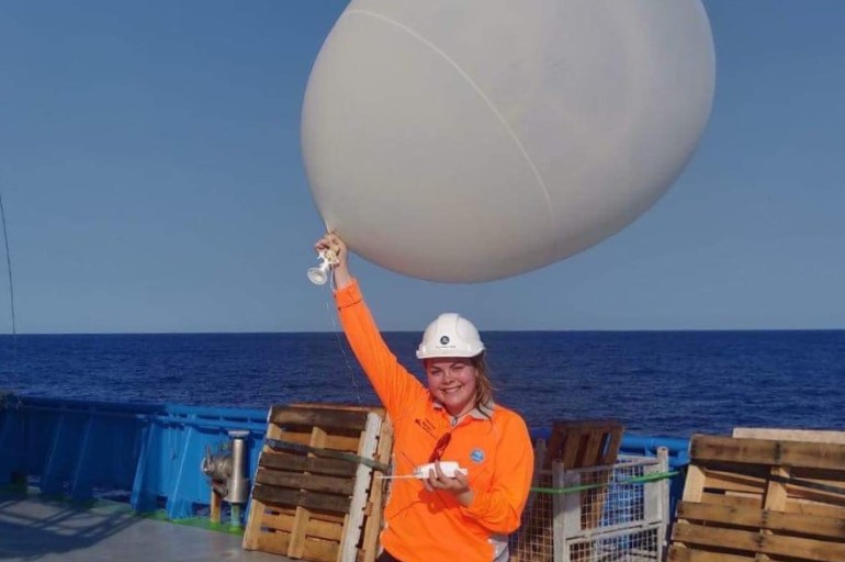 A person standing on the deck of a ship holding a weather balloon.