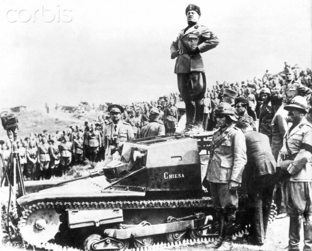 ca. 1939-1945 --- Il Duce stands on a tank to address troops during World War II. --- Image by © Corbis