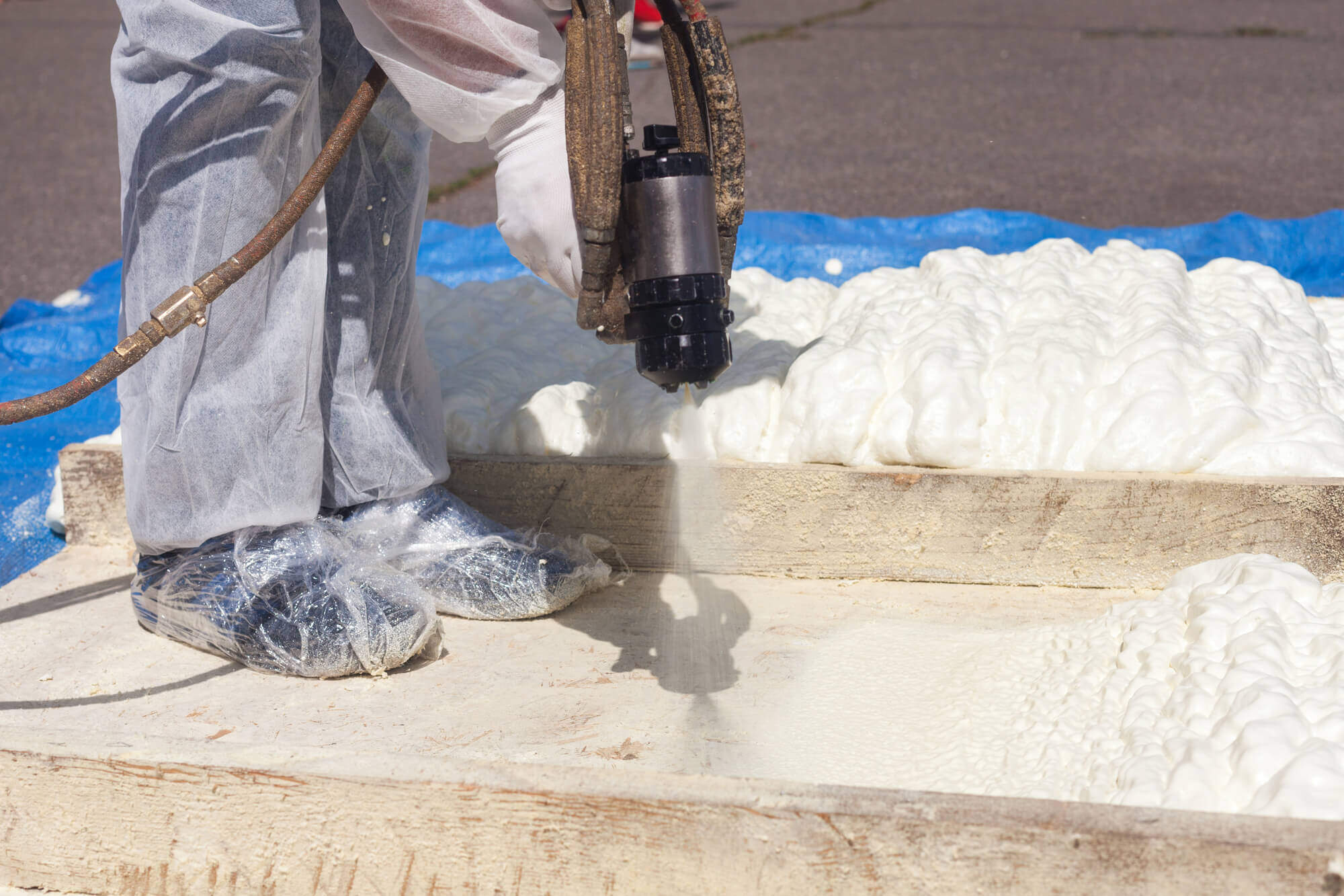 Technician spraying foam insulation using Plural Component Spray Gun.