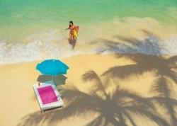 Girl carrying surfboard onto beach