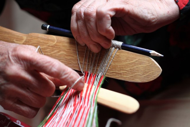 Laima used her wooden weaving knife, a pencil and thick household string to make the heddle. The string is placed under the bottom yarns and rotated around the pencil to make loops with which the yarns can be lifted during weaving. The knife is used for making evenly sized loops and it is removed when all the loops are ready.