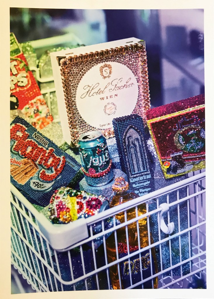 Image of gem-encrusted everyday shopping items in a shopping cart