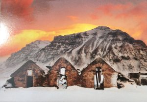 image of burned houses against a massive snowy mouintain