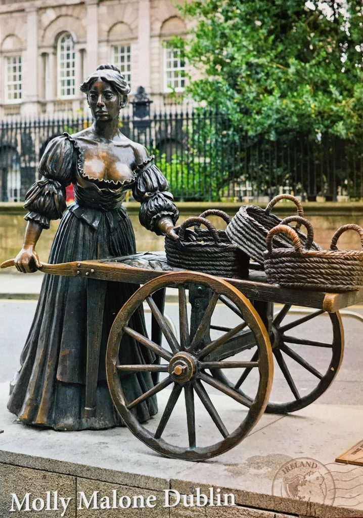 image of a brass statue of a woman with a cart