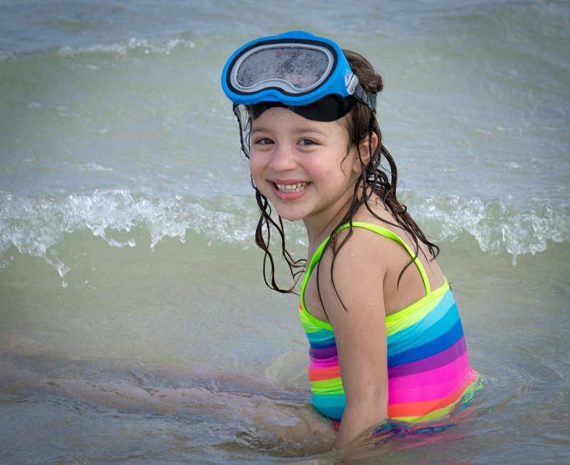 Niña sentada en el mar en la playa.