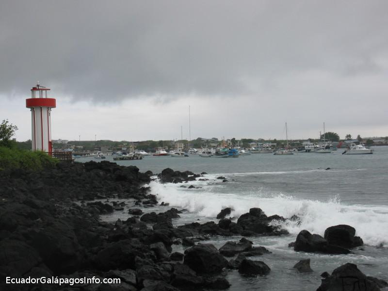 Vista desde la playa hacia el faro y el puerto de Puerto Baquerizo Moreno.