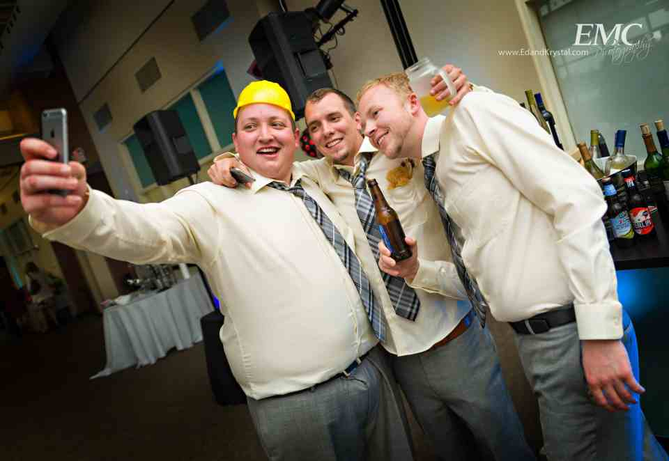 Three groomsmen take an iPhone selfie during a break in the dancing, one is wearing a construction hat from having performed the YMCA dance by the Village People.