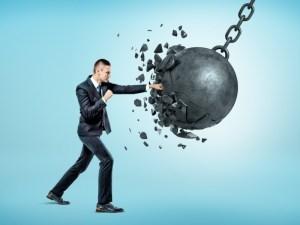 man punching and shattering wrecking ball