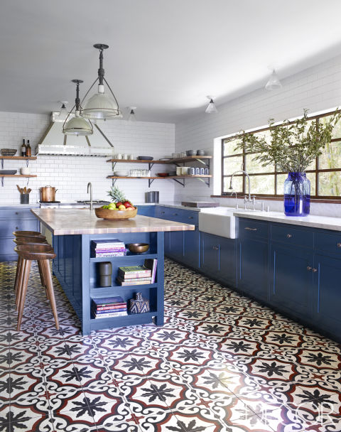 A blue kitchen island echoes the blue detailing in flooring by Granada Tile in this Hollywood Hills home. The vintage pendants are from Obsolete, the BassamFellows stools are from Design Within Reach, and the sink is by Shaws with fittings by Jaclo. The countertops are Carrara marble.