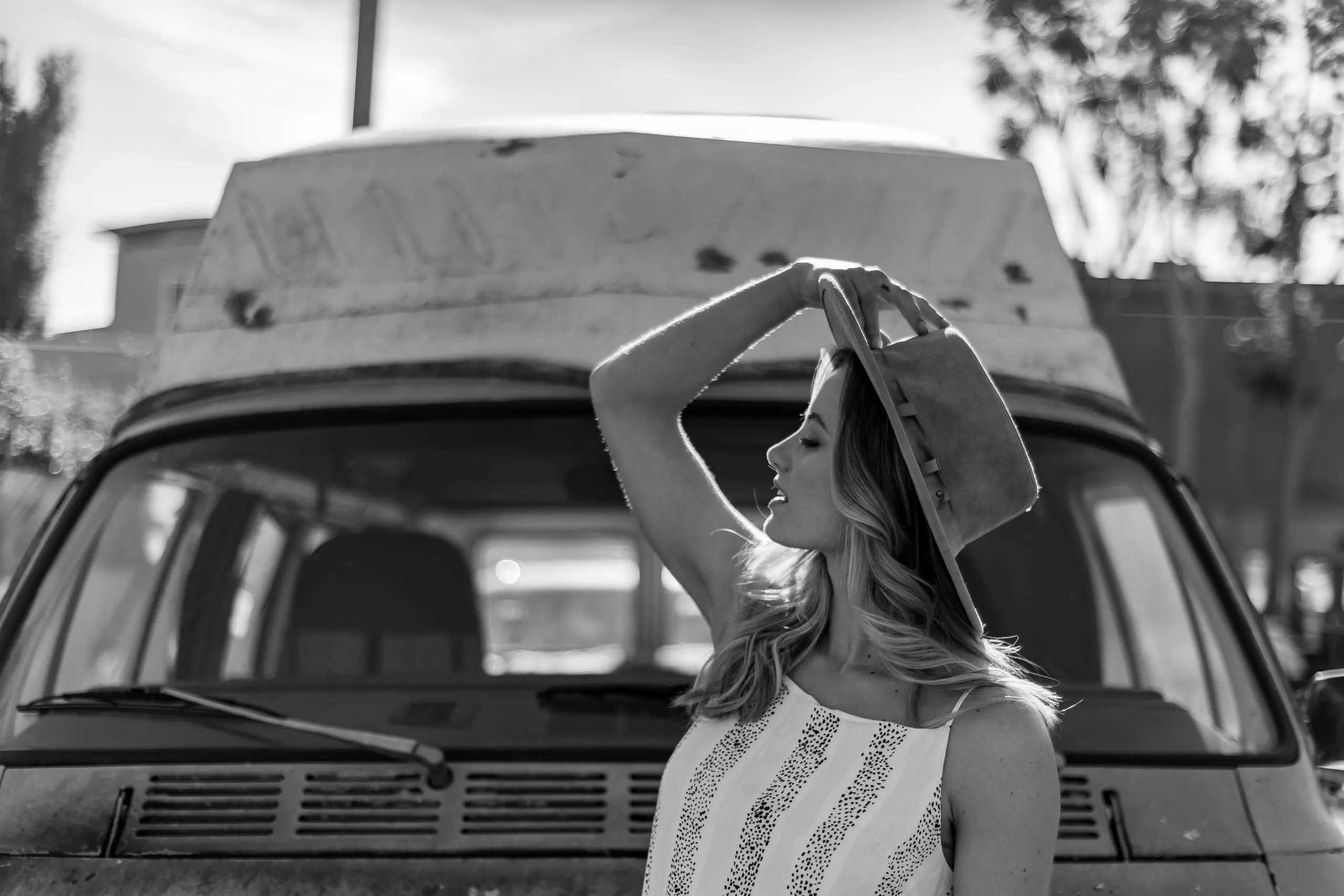 Carly Lane posing with a striped light blue and yellow sun dress in front of an old caravan van that is light brown. Sun flair is used to give the photo a cool blueish tone and cool feel to it.