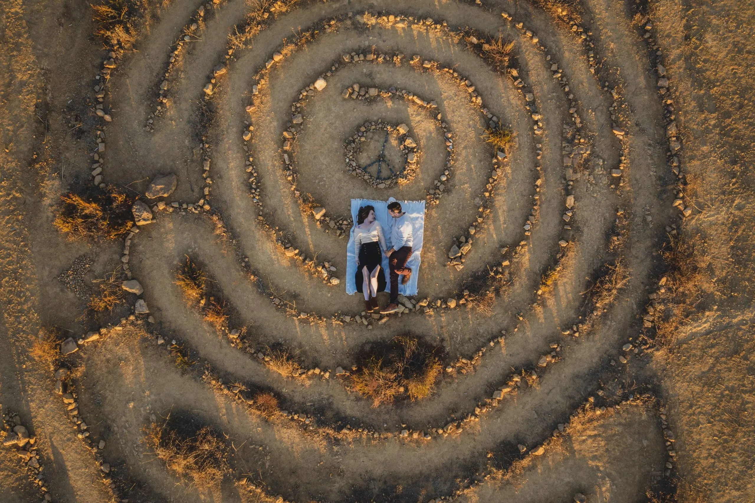 Top down view of couple laying down on a rock maze.