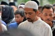 HR Amos, seorang kerabat Almarhum HM Sani, bersama sejumlah pelayat berdiri di sisi makam saat prosesi pemakaman di Taman Makam Pahlawan Batu 5, Tanjungpinang, Sabtu (9/4/2016). Foto: eddy mesakh.