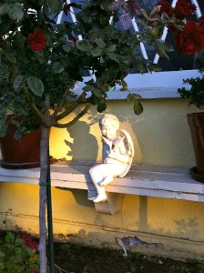 Garden cherub positioned in garden to catch the sunlight