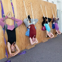 Students hanging in headstand from the rope wall.